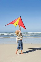 Boy 6-8 holding up kite on beach, side view