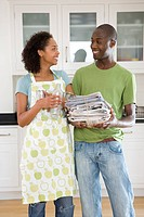 Young couple with recycling in kitchen smiling at each other, woman in apron