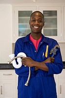 Plumber with wrench and pipes in kitchen, smiling, portrait
