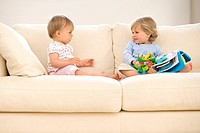 Baby girl 9-12 months looking at toddler boy 12-15 months on sofa with toys, side view