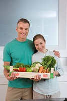 Couple in kitchen with box of vegetables, smiling, portrait