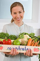 Woman with box of vegetables, smiling, portrait, close-up