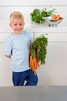 Boy with bunch of carrots in kitchen, smiling, portrait, elevated view (thumbnail)