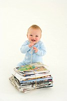 Baby boy 3-6 months by bundle of newspapers, smiling, elevated view