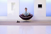 Businessman meditating in armchair in foyer, portrait (thumbnail)