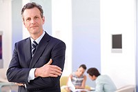 Businessman with arms crossed in office by colleagues having meeting, smiling, portrait