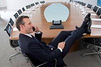 Businessman with feet up using telephone at head of conference table, smiling, side view