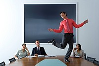 Businessman and women watching colleague dancing on boardroom table, smiling
