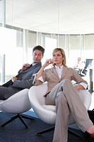 Businessman and woman in armchairs in office, man looking at woman