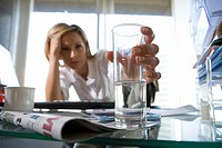 Young businesswoman at desk holding glass with soluble tablet, head in hand, focus on glass differential focus