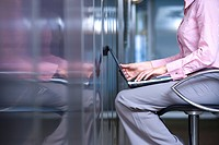 Businesswoman facing wall, laptop computer on lap, mid section, side view