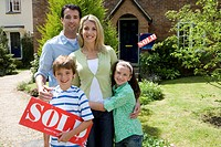 Family of four outside house, boy 8-10 with 'sold' sign, smiling, portrait