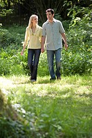 Young couple hand in hand in forest, low angle view (thumbnail)