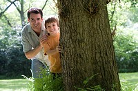 Father and son 8-10 peeking out from behind tree, smiling, portrait