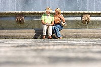 Senior couple sitting by fountain, ground view