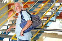 Senior man with gym bag by stairs, portrait, side view