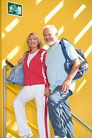 Senior couple walking up stairs with gym bags, smiling, low angle view