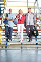 Two senior men and woman with gym bags walking down steps, smiling, portrait