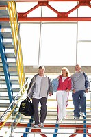 Two senior men and woman with gym bags walking down steps, low angle view