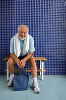 Senior man in gym changing rooms, smiling, portrait (thumbnail)