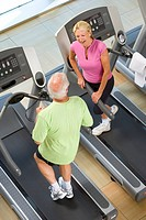 Senior man and woman on treadmills, having conversation, elevated view