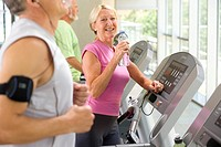 Mature woman on treadmill with water bottle, smiling, portrait