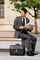 Businessman with briefcase and newspaper on park bench, looking over shoulder