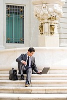 Businessman with briefcase using laptop computer on steps outdoors