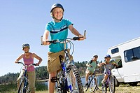 Family of four on bicycles by motor home, close-up of boy 10-12, low angle view