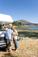 Mature couple by lake and motor home taking photograph of themselves with mobile phone