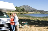 Couple by lake and motor home taking photograph of themselves with mobile phone