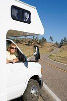Woman leaning out of window of motor home, smiling, portrait (thumbnail)