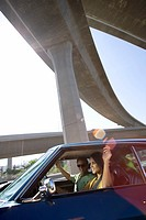 Young couple in car beneath overpass, smiling lens flare