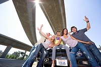 Medium group of friends on bonnet of car beneath overpass, smiling, portrait, low angle view sun flare
