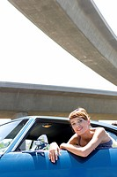 Young woman leaning out of window of car beneath overpass, smiling, portrait (thumbnail)