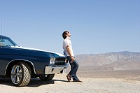 Young man with water bottle in sunglasses by car in desert, looking up, side view