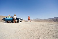 Small group of friends by car in desert, looking at view, low angle view