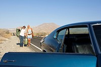 Young couple hitchhiking on desert road, approaching car with door open