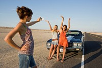 Young woman taking photograph of friends with arms raised by car on desert road