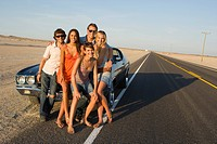 Medium group of friends by car on desert road, smiling, portrait
