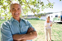 Mature man with arms crossed by wife and motor home outdoors, smiling, portrait