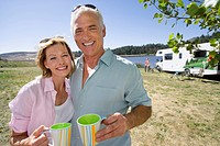 Mature couple with mugs by motor home and lake, smiling, portrait