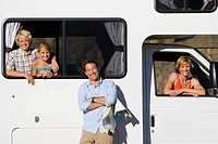 Father by family in motor home, son and daughter 8-12 in back, wife in drivers seat, portrait