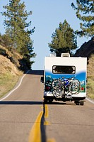 Motor home with bicycles on back on open road, rear view