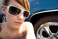 Young woman in sunglasses by car, close-up