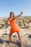 Young woman taking photograph in desert, man in background