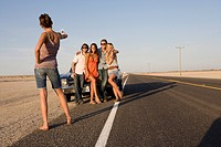 Young woman taking photograph of medium group of friends by car on open road, low angle view