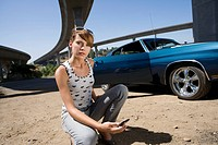 Young woman with mobile phone crouching by car, portrait