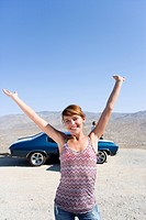 Young woman with arms raised by car in desert, smiling, portrait
