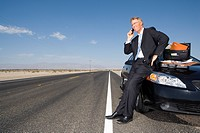 Businessman using mobile phone by briefcase and paperwork on car on side of road, low angle view